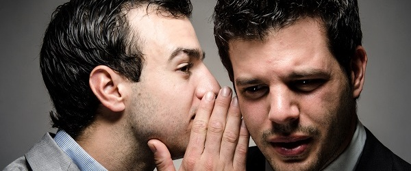 Men whispering to each other